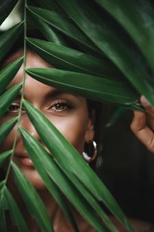 Gros plan du visage de femme bronzée caucasienne sans maquillage, se cachant derrière des feuilles tropicales de palmiers et souriant, furtivement à la caméra.