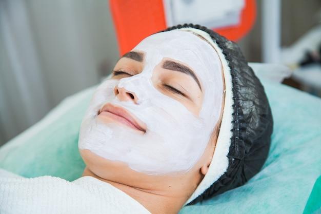 Gros plan du visage de femme dans la procédure de masque d'argile blanche dans un salon de beauté. masque peeling pour le visage, traitement de beauté spa, concept de soins de la peau.