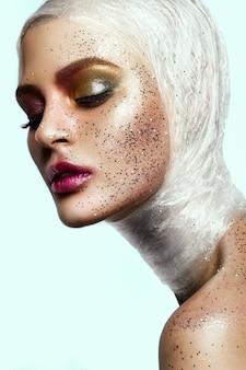 Gros plan du visage de femme avec des paillettes sur le visage