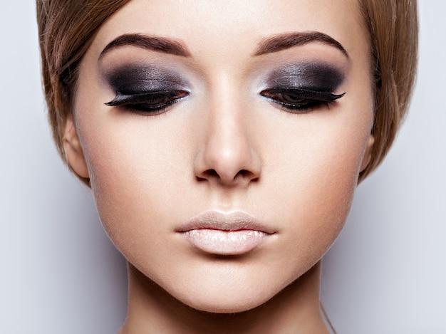 Gros plan du visage de la jeune fille avec de longs cils noirs. maquillage de mode