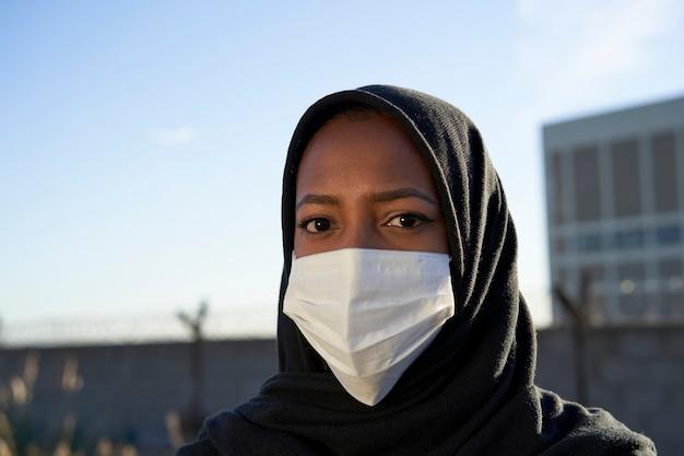 Gros plan du visage d'une jeune fille musulmane avec hijab et masque en regardant la caméra.