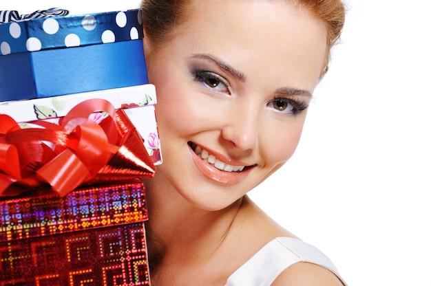 Gros plan du visage d'une jolie fille souriante avec les nombreux cadeaux