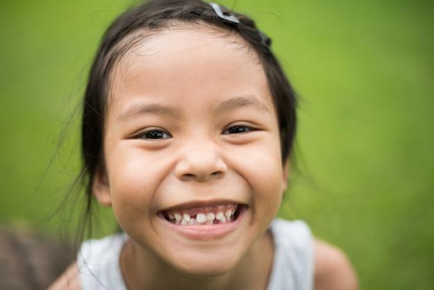Gros plan du visage de la petite fille mignonne avec un sourire en regardant la caméra.