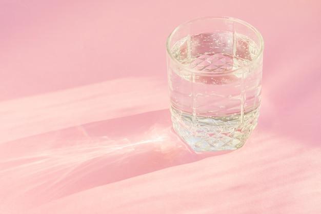 Gros plan d'eau gazeuse en verre transparent et de l'éblouissement du soleil sur fond rose.
