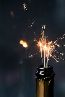 Gros plan, ébavurage, sparkler, bouteille vin, fond sombre