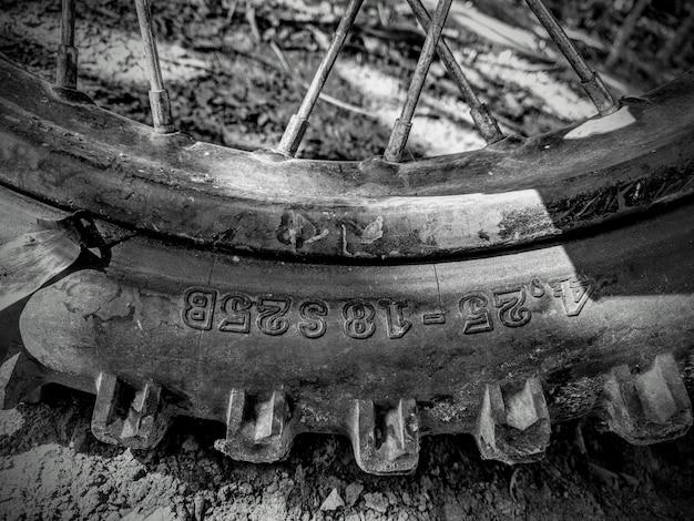 Gros plan sur l'échelle de gris d'un pneu de moto sur le sol boueux