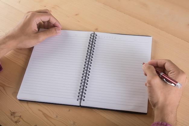 Gros plan de l'écriture d'homme d'affaires avec un cahier dans la table. concept de travail professionnel.