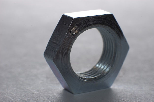 Gros plan d'un écrou métallique hexagonal chromé se dresse sur une surface de table