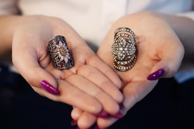 Gros plan d'une élégante bague avec des pierres sur les mains de la femme.