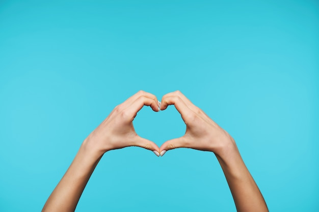 Gros plan sur d'élégantes mains levées formant coeur avec doigts isolés