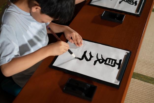 Gros plan sur des élèves faisant de la calligraphie japonaise, appelée shodo
