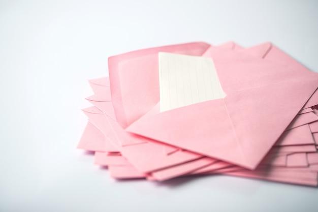 Gros plan d'empilage d'enveloppes roses et de papier à lettres mail sur fond blanc