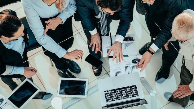 Gros plan des employés utilisant un ordinateur portable pour travailler avec des documents financiers