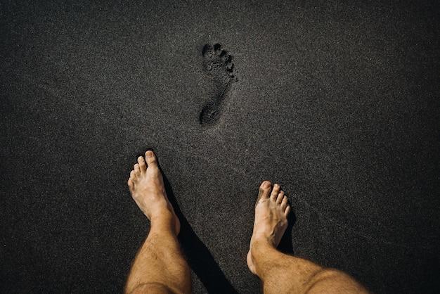 Gros plan des empreintes masculines et des pieds marchant sur le sable noir volcanique sur la plage.
