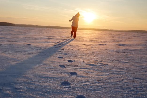 Gros plan des empreintes de pas dans la neige. la fille part vers le coucher du soleil.