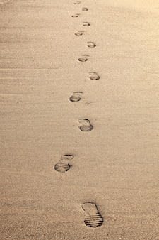 Gros plan des empreintes de pas dans le sable sur la plage.