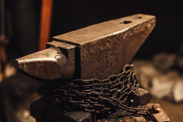 Gros plan d'une enclume de forgeron avec chaîne enroulée.