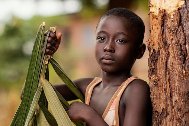 Gros plan, enfant africain, tenue, feuille