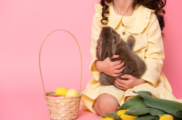 Gros plan enfant fille tenant lapin, tulipes, panier avec des oeufs colorés.