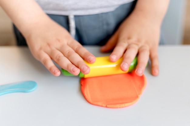 Gros plan enfant jouant avec de la pâte à modeler