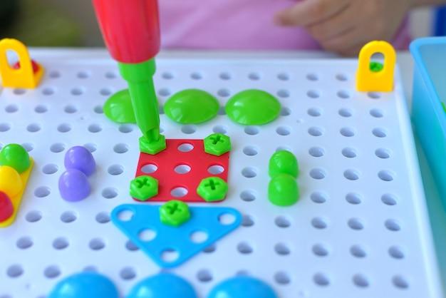 Gros plan d'un enfant jouant à un puzzle de constructeur éducatif pour enfants avec un tournevis, un tournevis et des shurukas avec des fiugs géométriques multicolores. concept créatif de développement des enfants d'âge préscolaire.