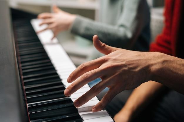 Gros plan d'un enfant méconnaissable jouant au piano, un professeur de musique s'assoit près et aide à jouer