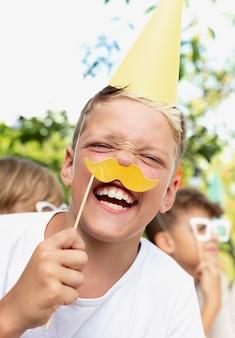 Gros plan d'un enfant souriant tenant une moustache