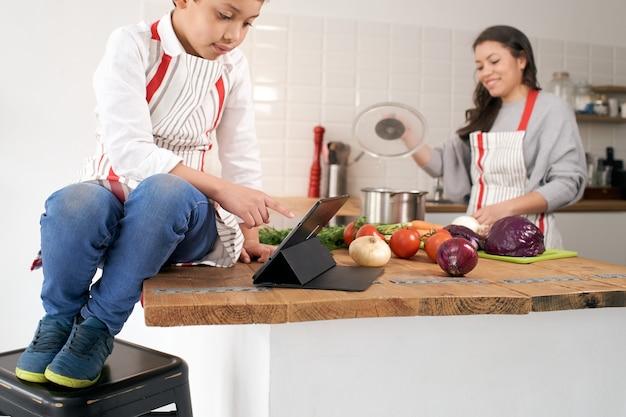 Gros plan d'un enfant en tablier dans la cuisine jouant avec une tablette pendant que la mère cuisine des légumes sains