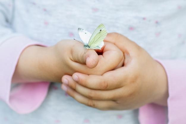 Gros plan enfant tenant soigneusement lady butterflyrelation et soins entre les enfants et les animaux