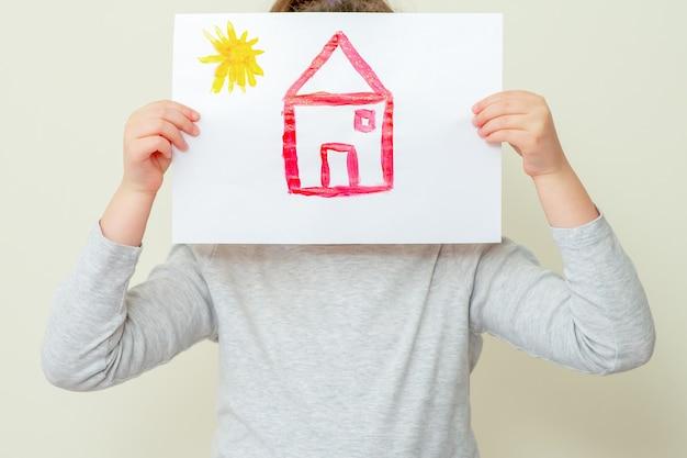 Gros plan de l'enfant tient une photo de la maison rouge avec le soleil couvrant son visage à l'école primaire. notion de peinture.
