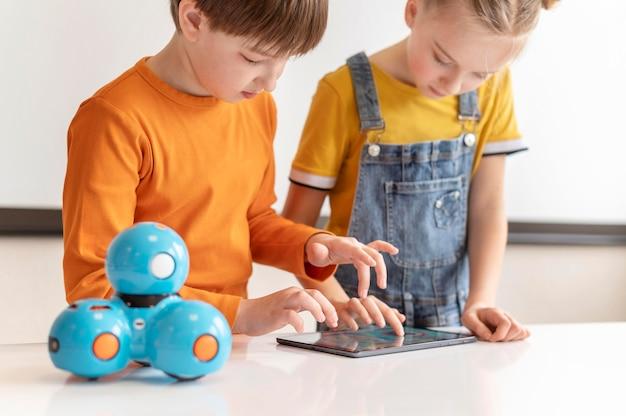 Gros plan des enfants apprenant avec tablette