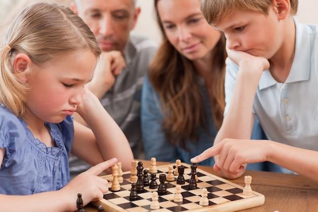 Gros plan d'enfants jouant aux échecs devant leurs parents