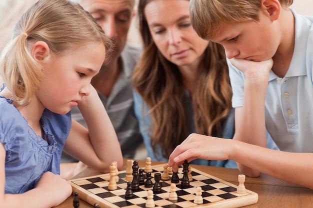Gros plan d'enfants sérieux jouant aux échecs en face de leur par
