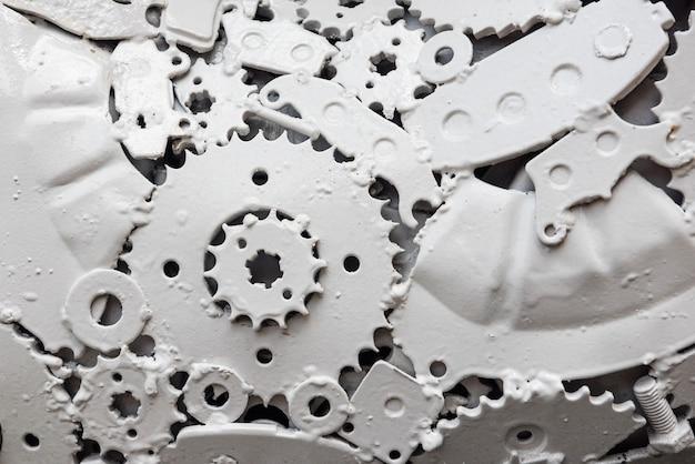 Gros plan sur des engrenages métalliques et des pièces de machine peintes en blanc. impression de fond texturé steampunk