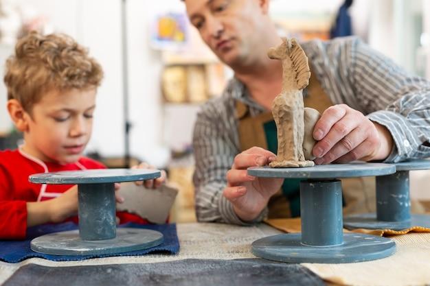 Gros plan de l'enseignant et des élèves sculptant des figures d'argile
