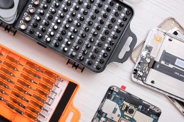 Gros plan sur un ensemble d'embouts de tournevis dans une boîte noire, des gants, des smartphones cassés et un ensemble d'outils pour remplacer le verre d'un téléphone et d'une tablette