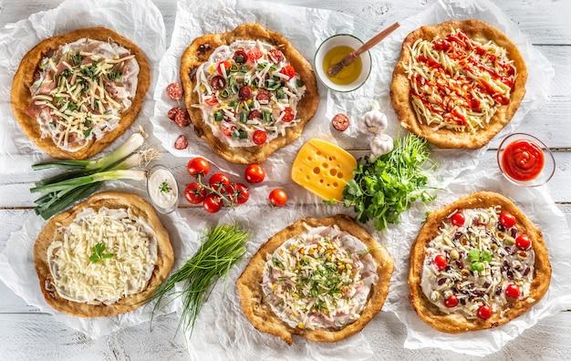 Un gros plan sur un ensemble de langos traditionnels hongrois avec des bords d'ail croustillants servis avec des légumes, des saucisses à la crème, des herbes, du râpé, du fromage, du ketchup, des trempettes et de l'huile.