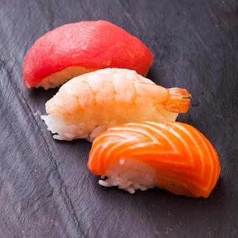Gros plan sur un ensemble de sushis aux arbres avec du saumon, du thon et des crevettes sur une ardoise