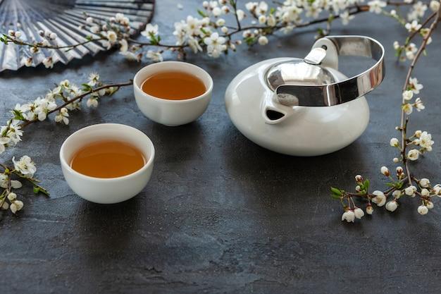Gros plan d'un ensemble de thé asiatique en porcelaine blanche avec du thé vert du japon