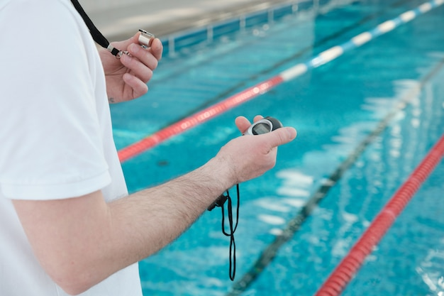 Gros plan d'un entraîneur méconnaissable tenant un sifflet et à l'aide d'un chronomètre à l'entraînement de natation
