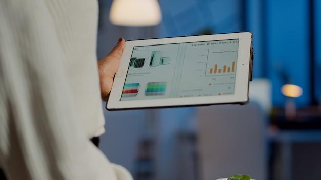 Gros plan d'un entrepreneur noir analysant les rapports financiers en zoomant debout dans le bureau de démarrage tard dans la nuit tenant un ordinateur portable. employé africain travaillant en vérifiant les statistiques surmenant l'écriture, la recherche.