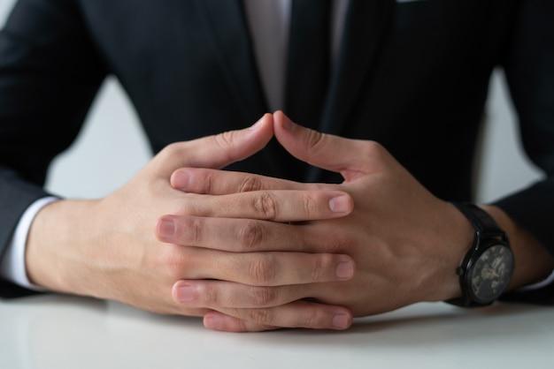 Gros plan d'un entrepreneur pensif avec les mains jointes