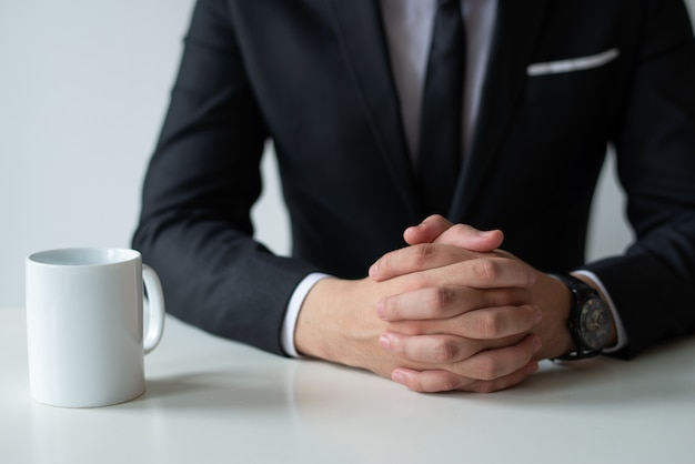 Gros plan d'un entrepreneur réfléchi avec les mains jointes