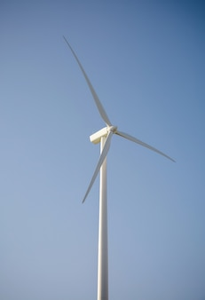 Gros plan de l'éolienne et des pales générant de l'électricité sur un fond de ciel bleu. concept de production d'énergie propre et écologique.
