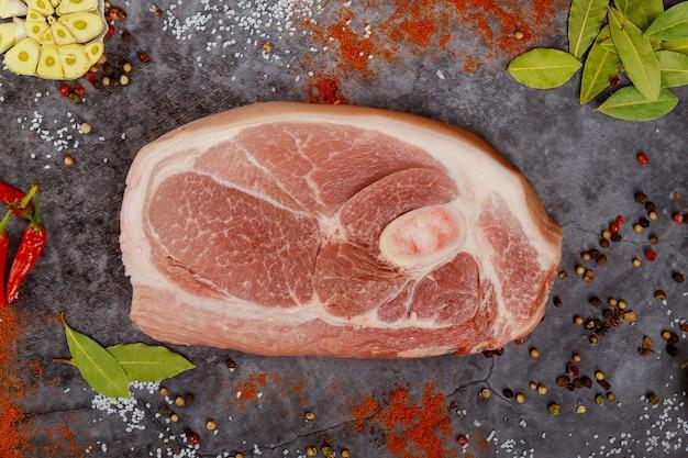 Gros plan sur une épaule de porc crue tranchée avec des épices sur une surface sombre. vue de dessus.