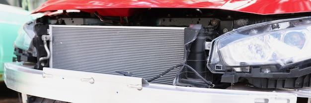 Gros plan d'une épave de voiture rouge en atelier de réparation