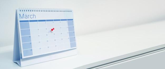 Gros plan d'une épingle sur le calendrier de bureau vierge.