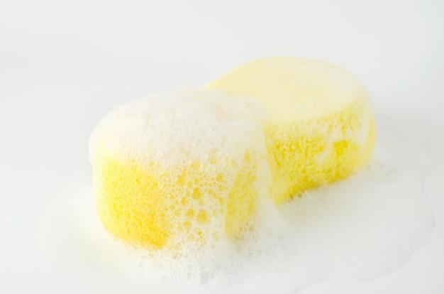 Gros plan d'une éponge jaune avec de la mousse de savon et des bulles sur fond blanc