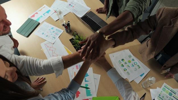 Gros plan sur une équipe diversifiée et heureuse d'hommes d'affaires réunis applaudissent et célèbrent le succès au travail d'équipe du groupe d'affaires de bureau dans l'espace de coworking de style de vie