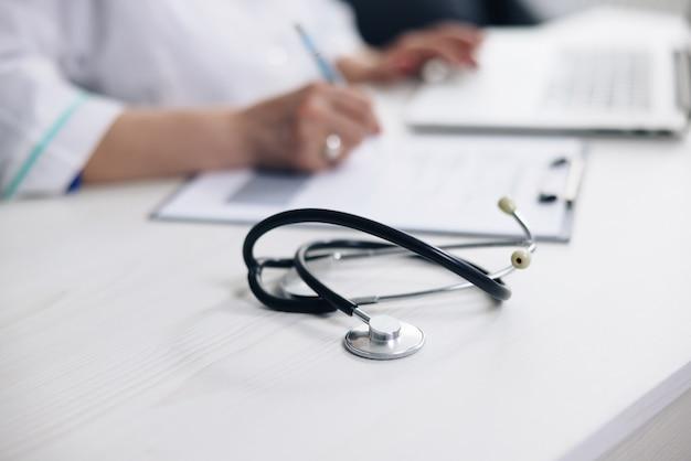 Gros plan sur un équipement médical stéthoscope avec une femme médecin travaillant